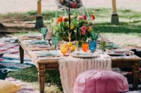 20 a very colorful picnic setting with bold blooms, glasses, plates and rugs and pillows will do both for a wedding or a bridal shower