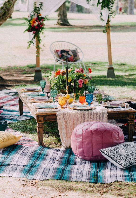 a very colorful picnic setting with bold blooms, glasses, plates and rugs and pillows will do both for a wedding or a bridal shower