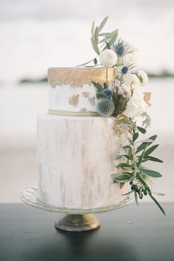 a watercolor gold wedding cake decorated with greenery, white blooms and thistles