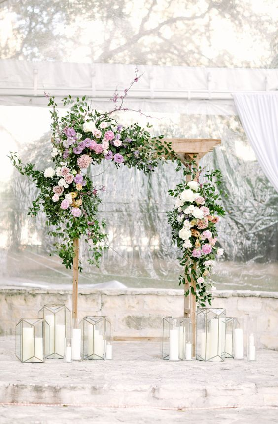 a wedding arch decorated with lilac, dusty pink, blush and creamy blooms and candles around
