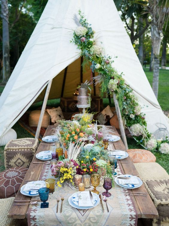 a boho picnic setting with Moroccan ottomans, an embroidered table runner, colorful wildflowers and herbs and pampas grass