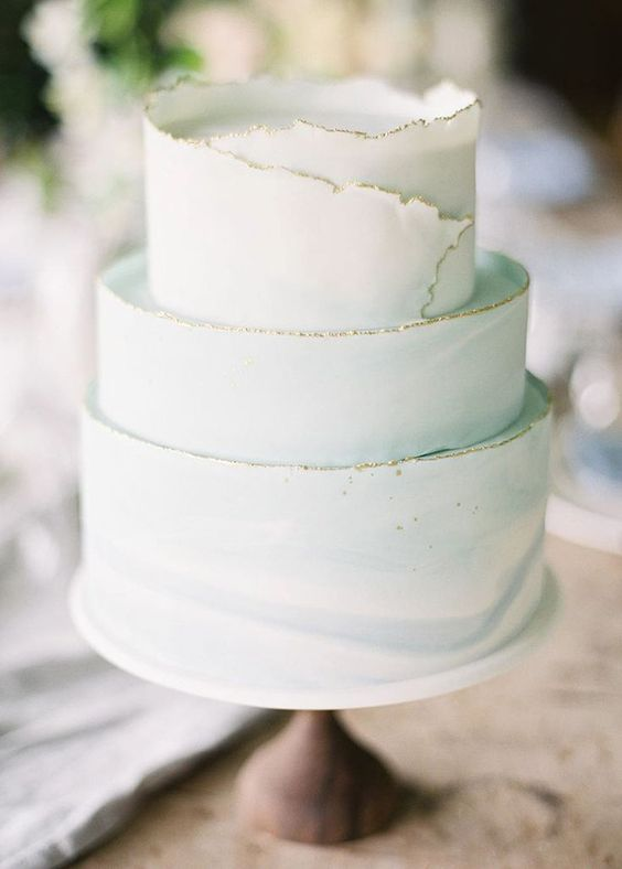 a light green wedding cake with a textural gold leaf egde is a very soft and tender idea