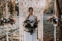 21 a macrame wedding backdrop with potted florals on both sides