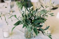 21 a sheer glass vase with greenery and olive branches with olives on them