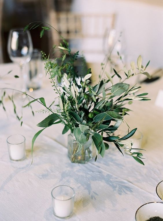 a sheer glass vase with greenery and olive branches with olives on them