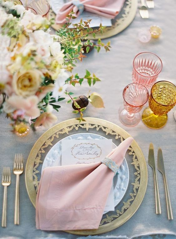 a table setting with pink and amber glasses, with a gold edge charger and gold and pink blooms