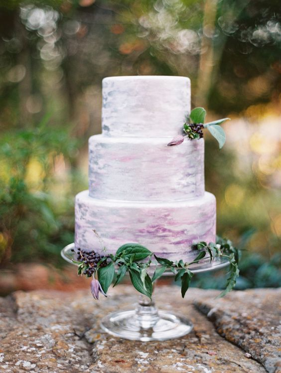 a watercolor lavender wedding cake topped with some berries for a boho or woodland wedding