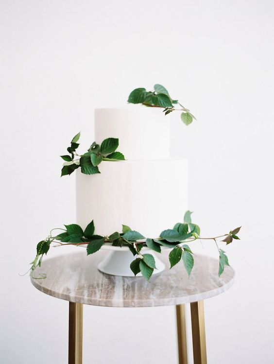 an elegant white cake with some foliage is ideal for a minimalist spring wedding