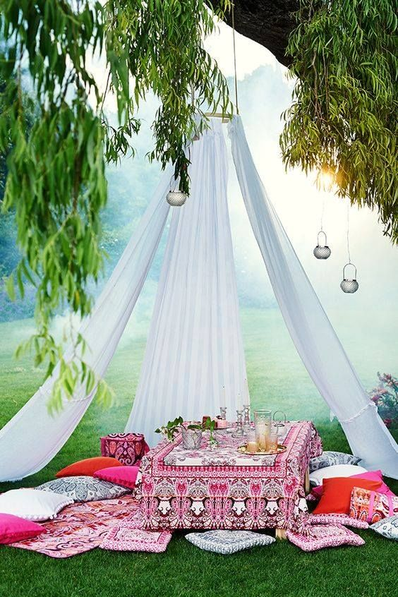 a dreamy and romantic picnic setting with a teepee with candle holders and a Moroccan styled chest as a table