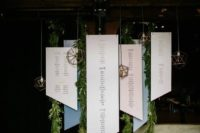 22 a hanging geometric seating chart with paper and acrylic parts and copper hanging lamps