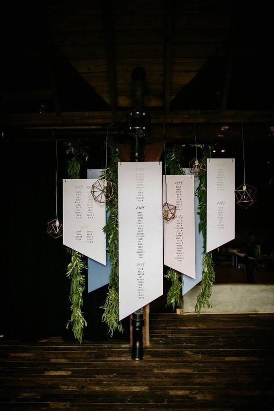 a hanging geometric seating chart with paper and acrylic parts and copper hanging lamps