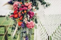 22 a lush colorful floral wedding arch with antlers and macrame hanging for a boho wedding