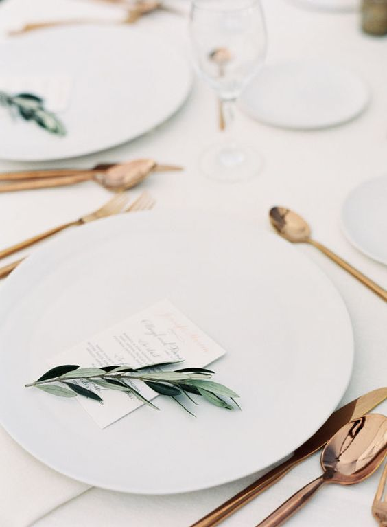 a minimalist tablescape with white chargers, copper cutlery, olive branches and simple menus