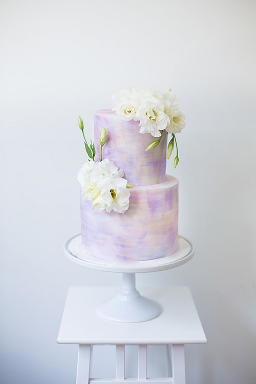 a pastel watercolor wedding cake topped with fresh white flowers