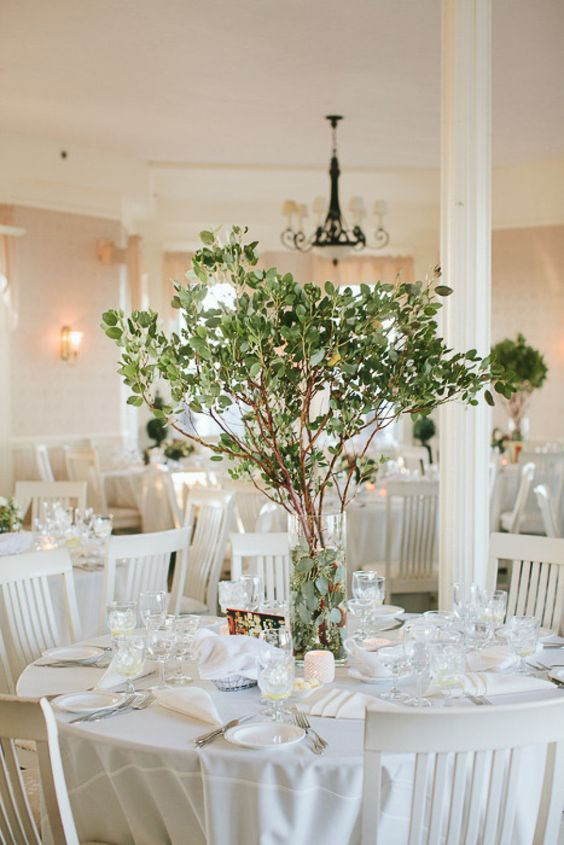 a simple yet stunning centerpiece with fresh greenery on branches is great idea for any season