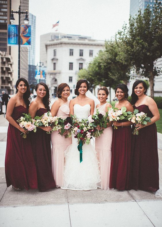bridesmaids wearing strapless marsala gowns and one shoulder blush ones