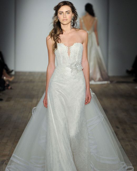 white strapless wedding gown with a covered plunging neckline, a flower on the waist and a detachable skirt by Lazaro