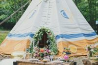 23 a glamping elopement setting with a teepee decorated with blooms, a pallet table with lush florals and candles and faux fur pillows