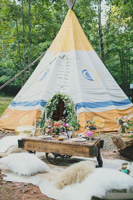 a glamping elopement setting with a teepee decorated with blooms, a pallet table with lush florals and candles and faux fur pillows
