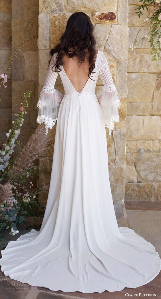 a long boho lace dress with a V cut back, long bell lace trim sleeves and a train