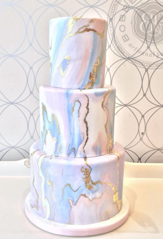 a marbleized pink and blue wedding cake with gold leaf touches