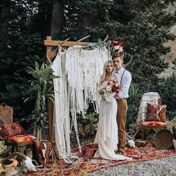 a wedding arch with antlers on top, lush blooms on one corner and several layers of macrame