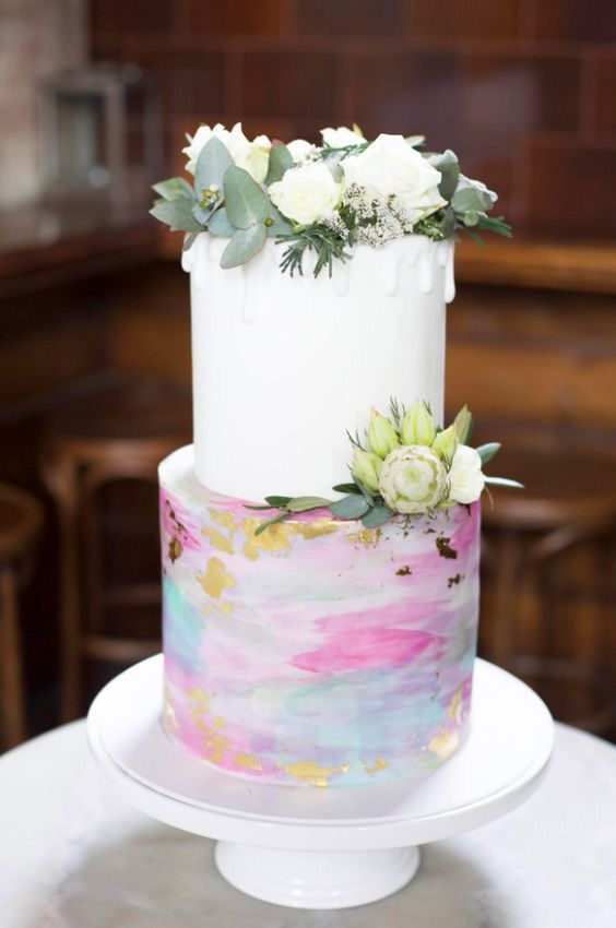 a wedding cake with a white tier and a bright watercolor one with gold leaf plus fresh blooms