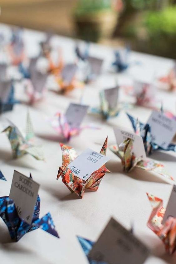 colorful paper cranes holding escort cards for a wedding - what a cute idea
