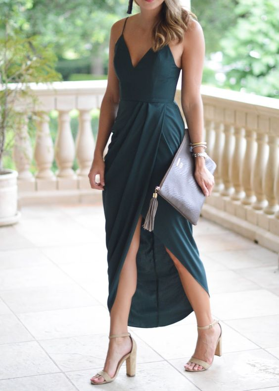 a draped dark green maxi dress with spaghetti straps, a wrap skirt with a slit, nude shoes and matching tassel earrings