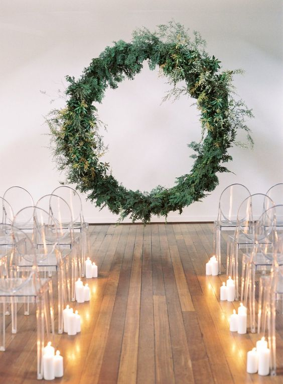 a minimalist wedding ceremony space with a suspended circle wedding arch, acrylic chairs and candles