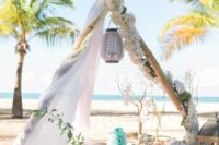 24 a ocean-inspired teepee setting with turquoise details and lush white blooms