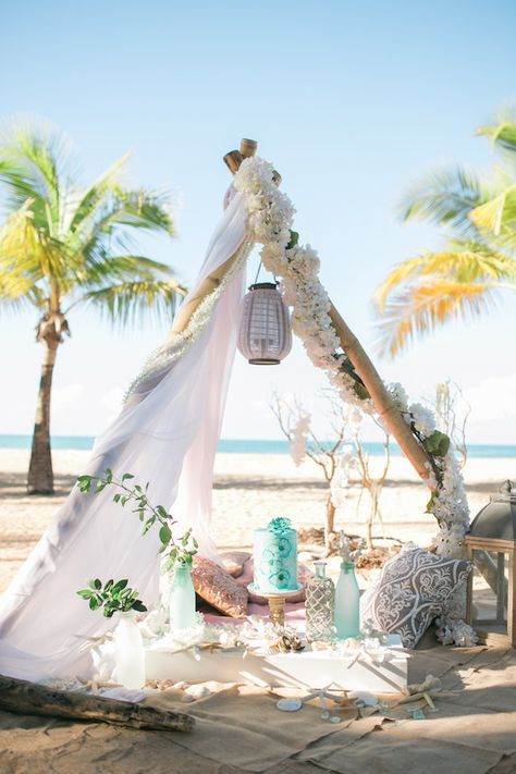 a ocean-inspired teepee setting with turquoise details and lush white blooms