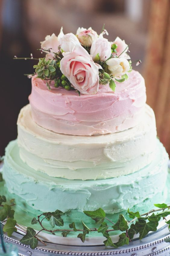 a pastel textural wedding cake with mint and pink tiers and fresh blooms on top
