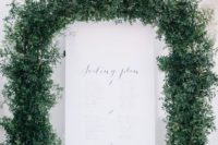 24 a printed seating plan surrounded with a large lush greenery garland for a fresh feel