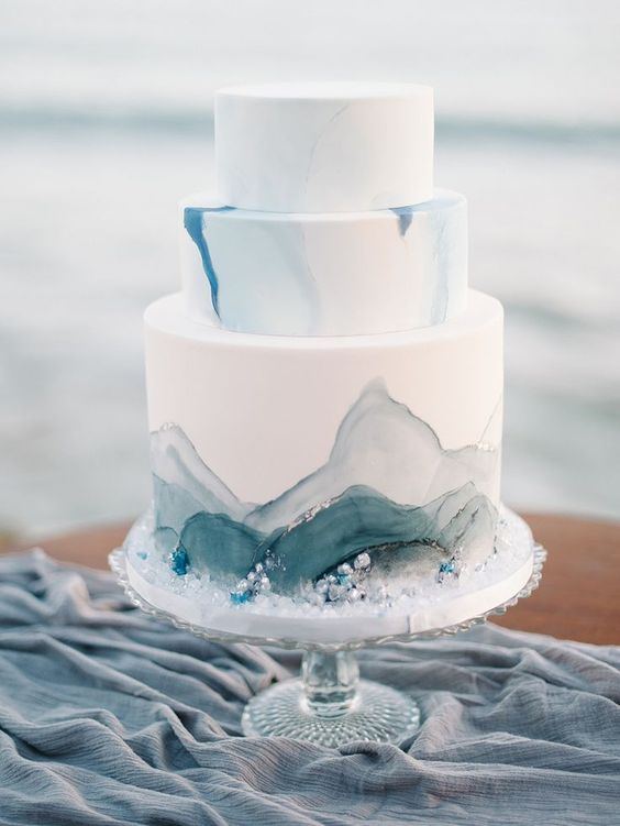 a watercolor grey and blue wedding cake decorated with edible pearls and beads for a seaside wedding