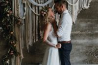 24 an indoor macrame wedding backdrop with lush blooms and greenery