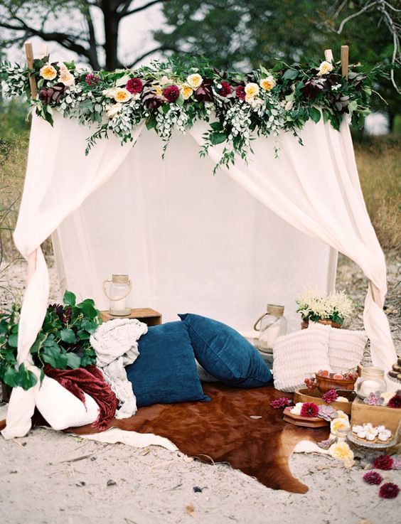 a teepee with lush florals and gorgeous textiles instead of a sweetheart table