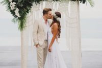 25 a tropical macrame wedidng backdrop with white orchids and lush tropical leaves