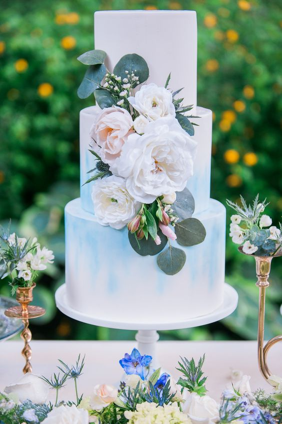 a white wedding cake with watercolor blue touches and lush florals