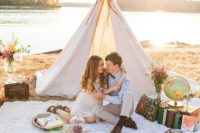26 a travel-inspired teepee setting with books, a globe and flowers for a cozy elopement