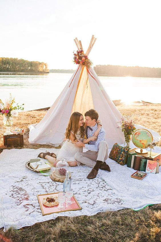 a travel-inspired teepee setting with books, a globe and flowers for a cozy elopement