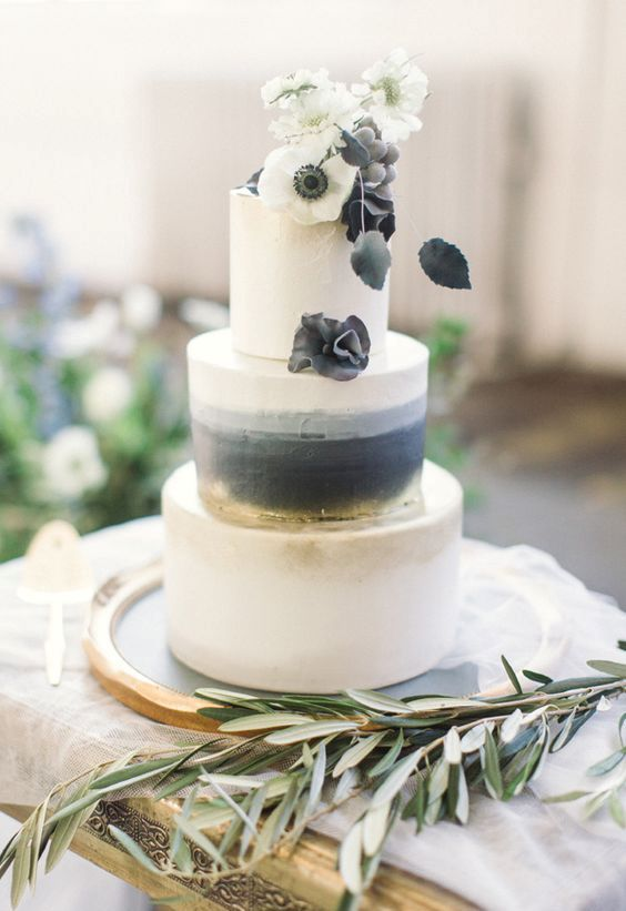 an elegant black, grey and white wedding cake with some watercolor and ombre plus black and white blooms