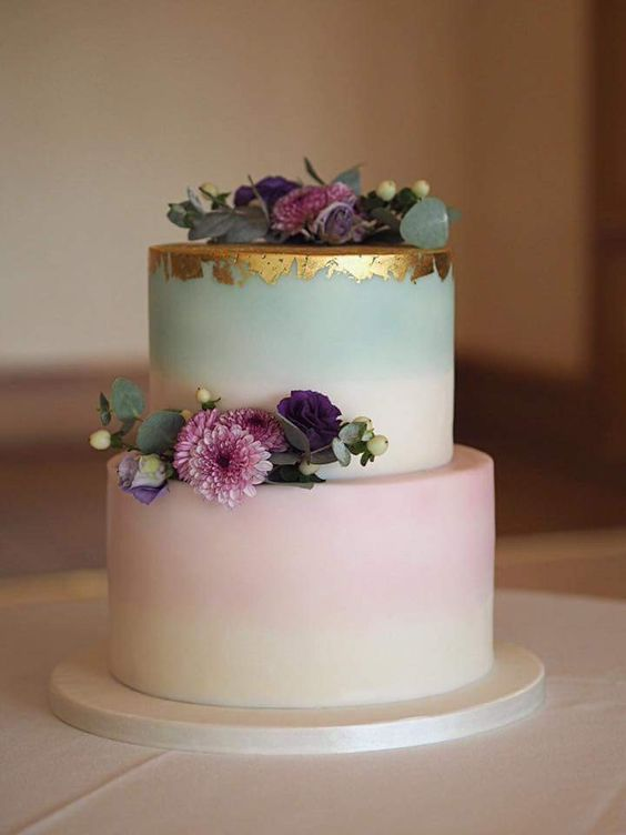 an ombre pastel wedding cake with a gold leaf top and fresh blooms for a quirky summer wedding