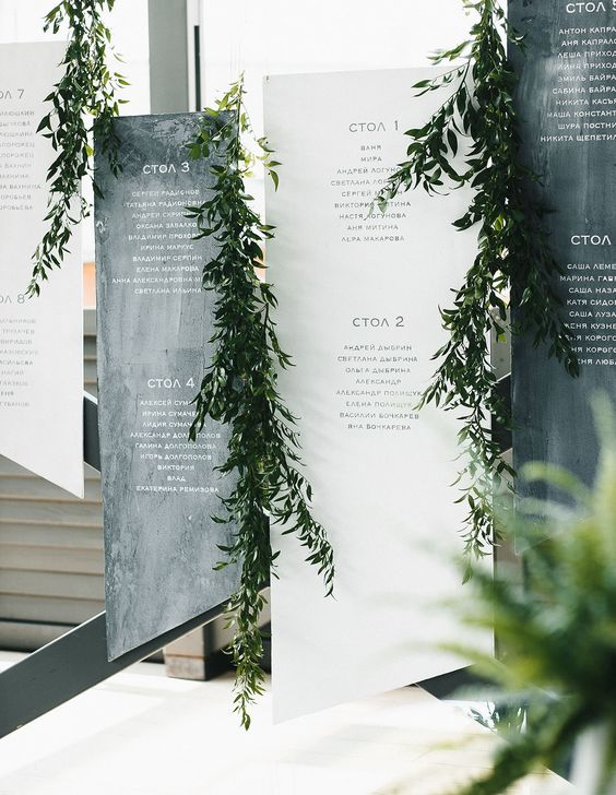 black and white geometric seating charts decorated with greenery garlands