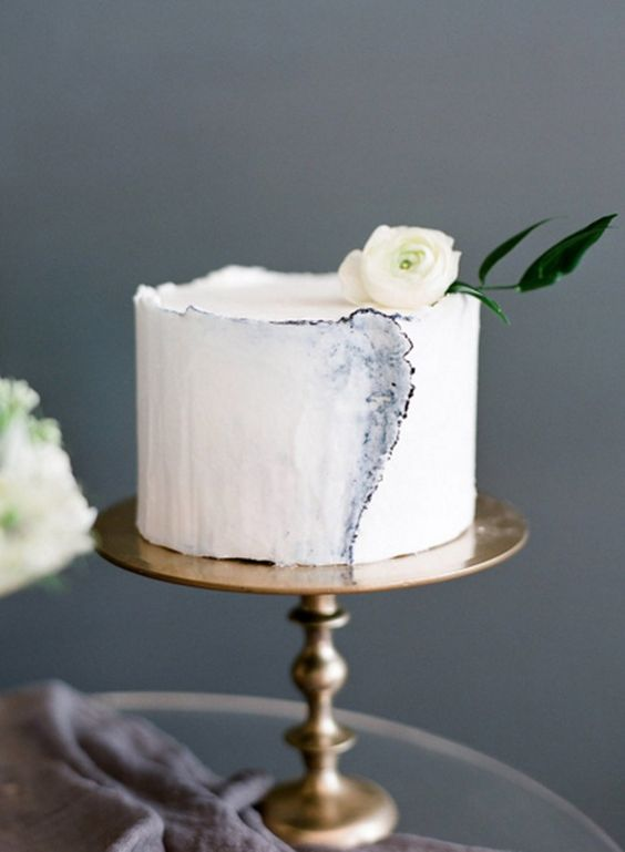 a blue edged watercolor cake with a small white bloom on top looks like a masterpiece