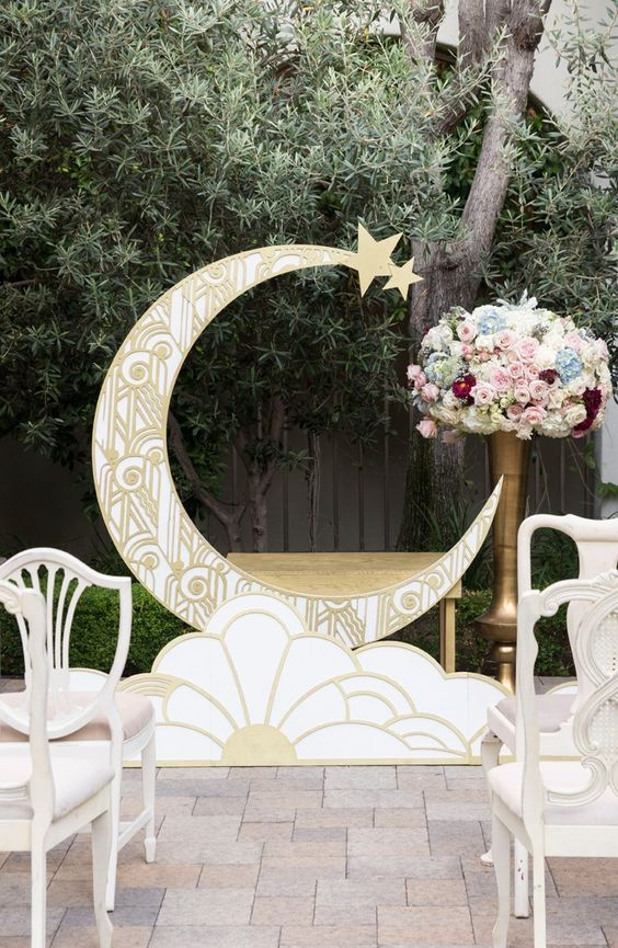 1920s inspired gold patterned crescent moon wedding backdrop with lush florals and refined chairs