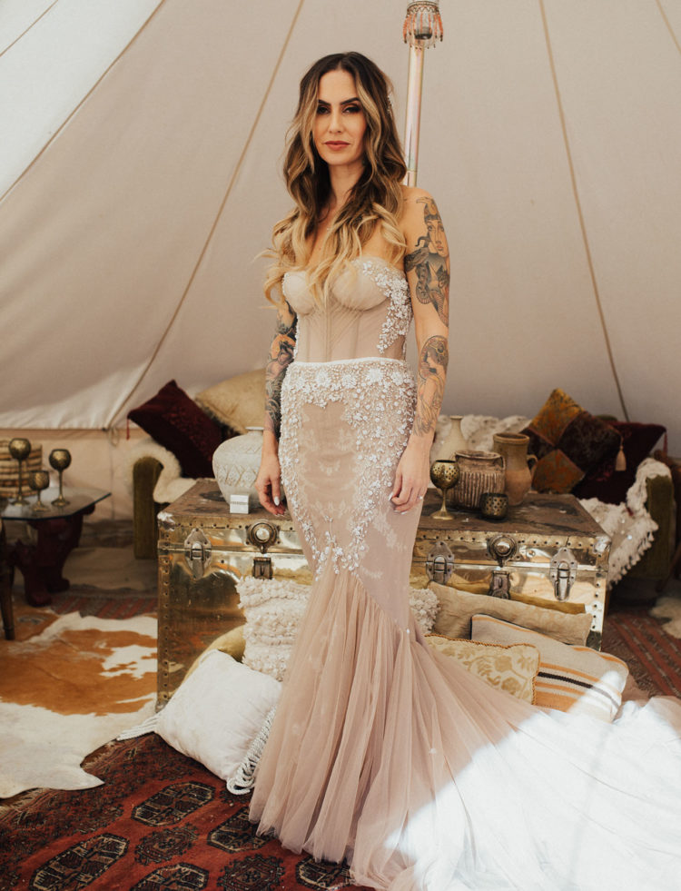 The bride was wearing a breathtaking blush mermaid wedding dress with rhinestones and beading, which showed her tattoos