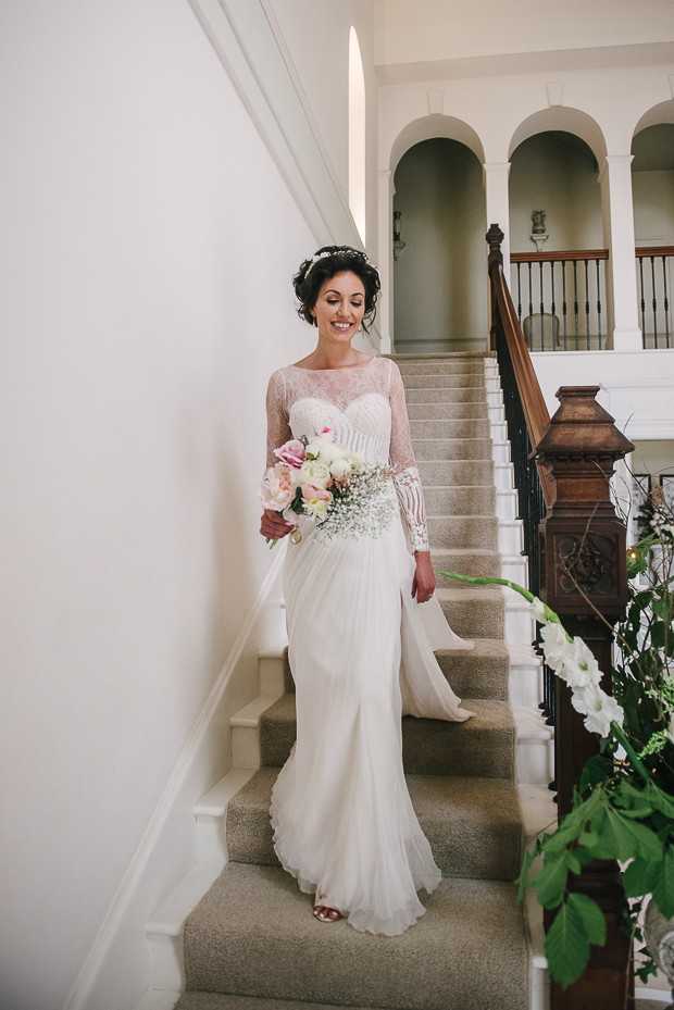 The bride was wearing a gorgeous wedding dress with an illusion neckline and sleeves and a dramatic side slit