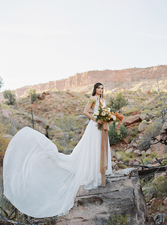 The bride was wearing a wide strap halter neckline wedding dress with an airy skirt and a train