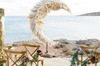 02 The wedding space was done with chairs with floral terrariums and a jaw-dropping pampas grass wedding altar shaped as a crescent moon